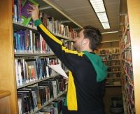 Library staff removing book from shelf