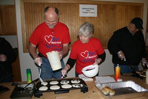 2 volunteers making pancakes