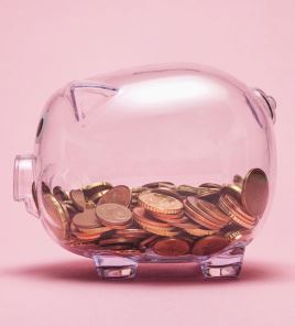 Clear piggy bank with pennies inside against pink background
