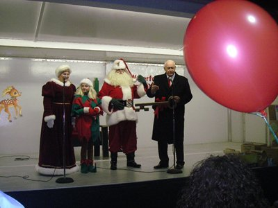 Santa, Mrs. Clause and an elf being introduced by a man