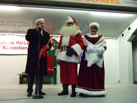 A man speaking next to Santa and Mrs. Claus