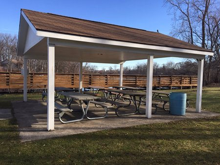 A covered patio area with picnic tables