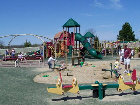 A colorful playground with families playing