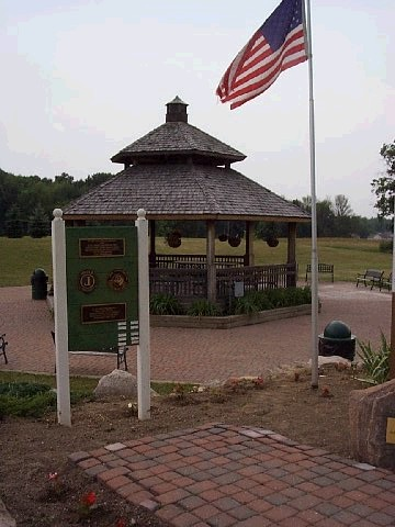 A gazebo with the American flag waving