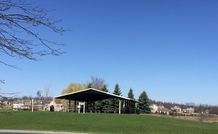 A large pavilion with picnic tables and a bright blue sky above