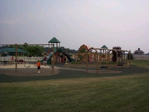 A playground with swings anda slide and turf
