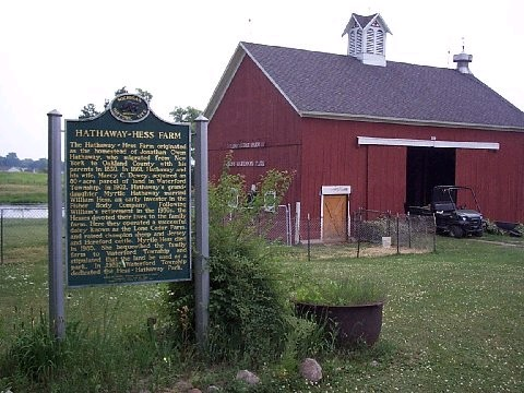 A red barn with a historical marker sign out front